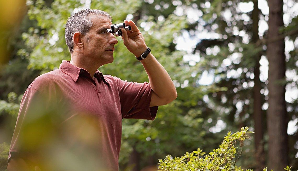 Hombre con binoculares en el bosque
