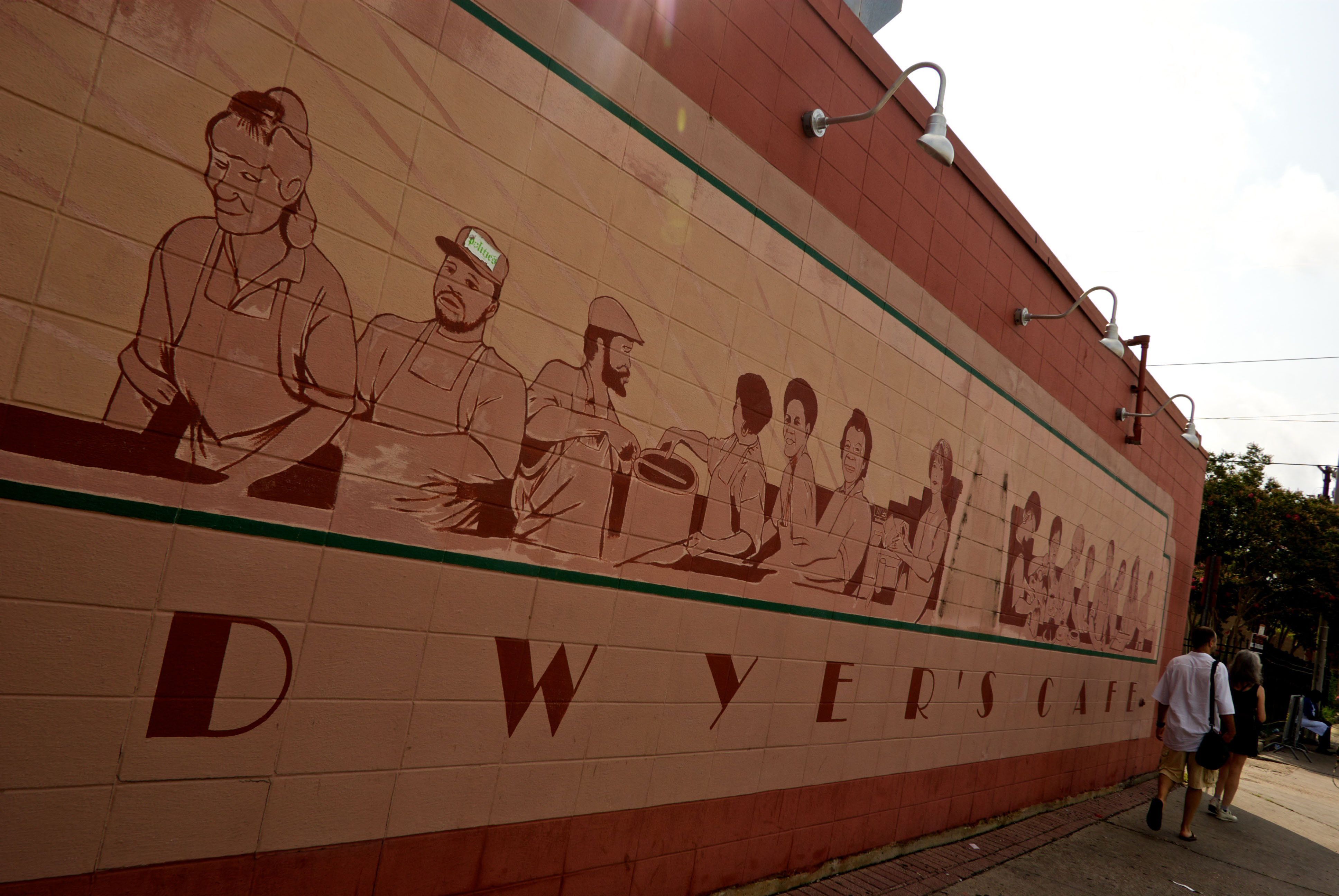 Tourists walking by big wall mural at Dwyer's Cafe in downtown Lafayette LA