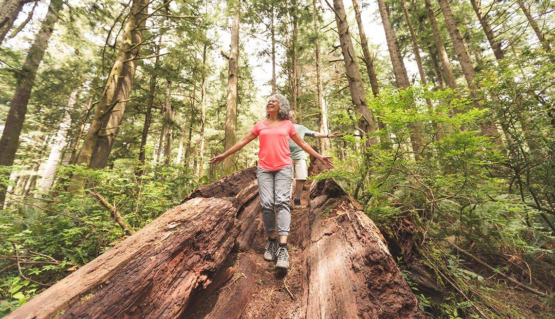 Pareja de adultos mayores caminan sobre un tronco en el bosque.
