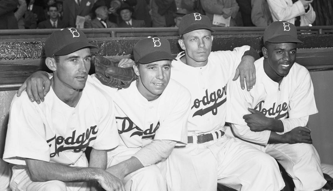 Jackie Robinson sentado en el banco con sus compañeros de equipo de los Dodgers de Brooklyn