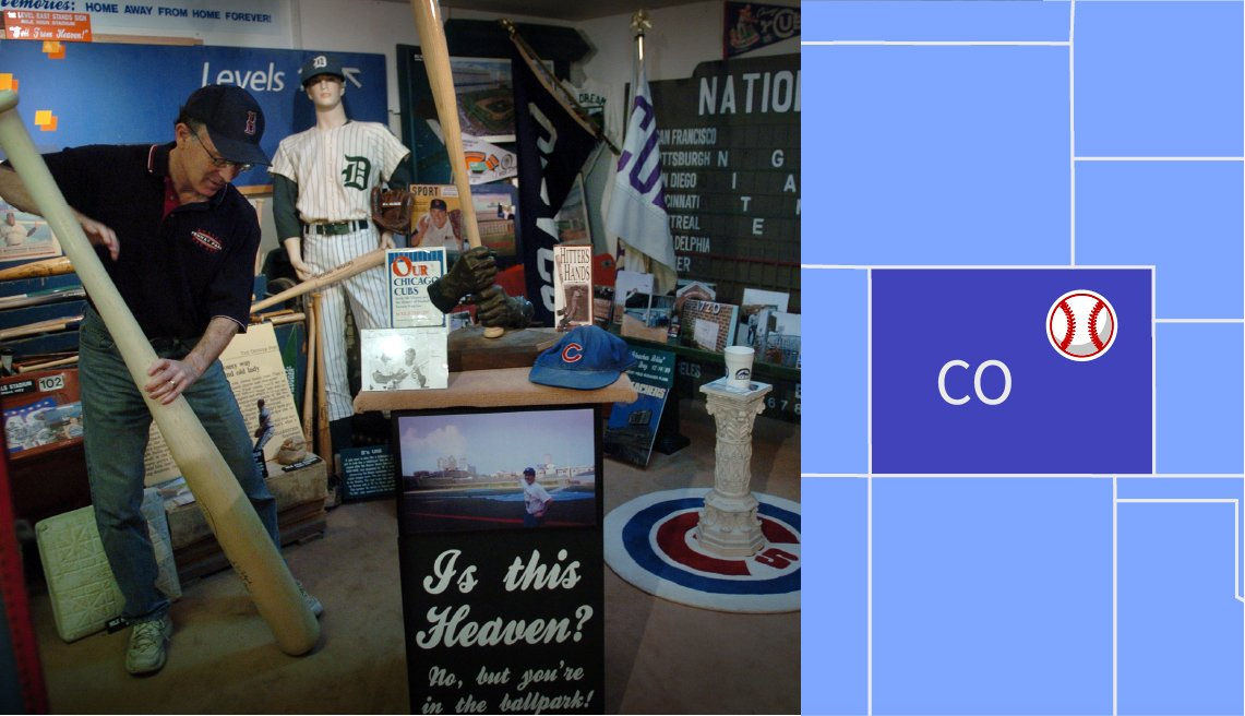 a photo of bruce hellerstein adjusting a giant baseball bat at the ballpark museum in denver colorado