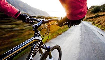 Hombre en una bicicleta en la Región de los Lagos del Reino Unido - Vacaciones en bicicleta puede ser una forma cultural y ambiental de ver el mundo