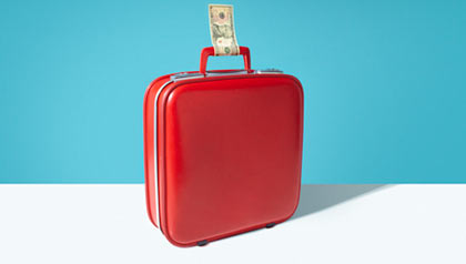 Red suitcase with dollar bill as luggage label