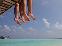 Pareja de pies en un muelle sobre una playa - Destinos atractivos para homosexuales