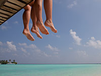 Couple's legs dangle from pier, beach and sea below