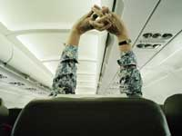 Stay healthy on a plane by stretching, even if seated
