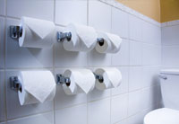 Six toilet paper rolls on tiled bathroom wall