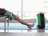 Consejos sobre lo que debe hacer cuando su vuelo ha sido cancelado - Piernas de mujer con una maleta en un aeropuerto