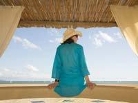 Cómo conseguir un upgrade - Mujer sentada viendo el mar.