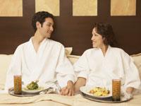 Un hombre y una mujer sentados en una cama - Cómo elegir una posada ideal para Ud.