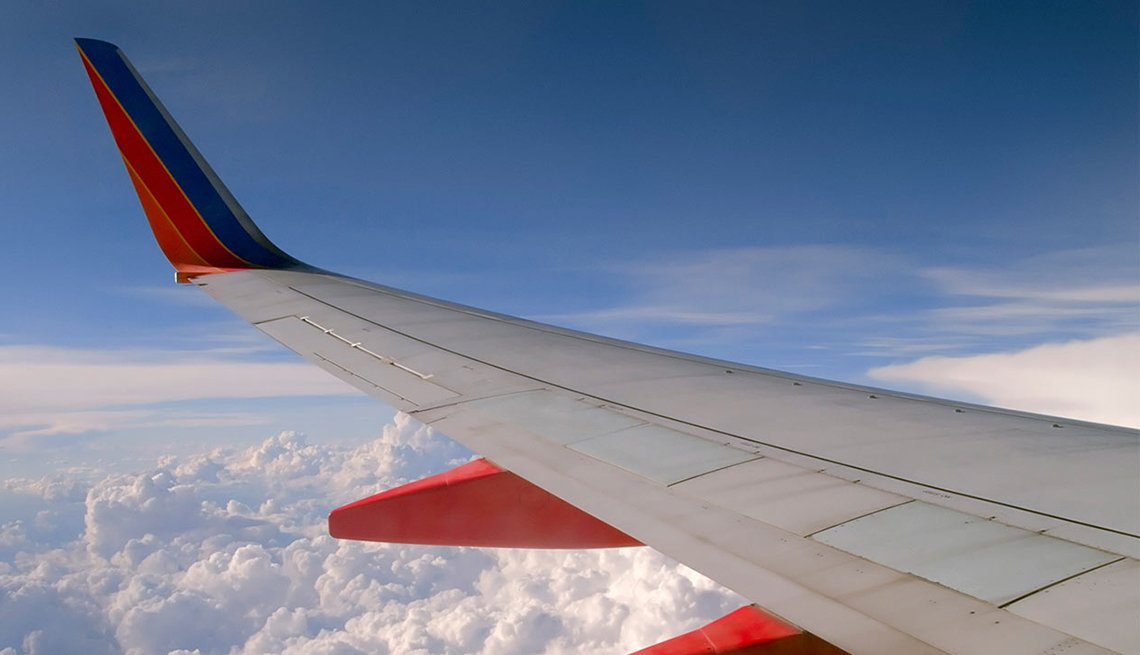 Aircraft Wing in Flight, Clouds, Blue Sky, Ridiculous Flying Fees and How to Avoid Them