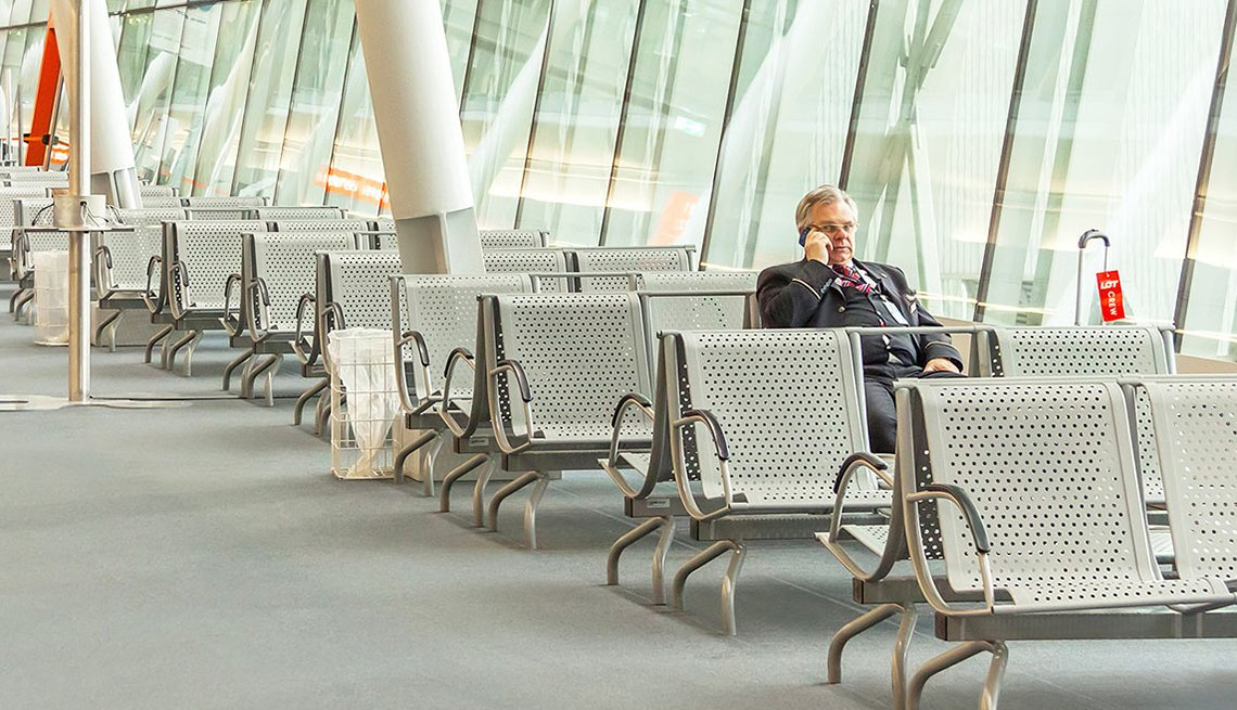Businessman on Phone in Empty Terminal Seats, Ridiculous Flying Fees and How to Avoid Them
