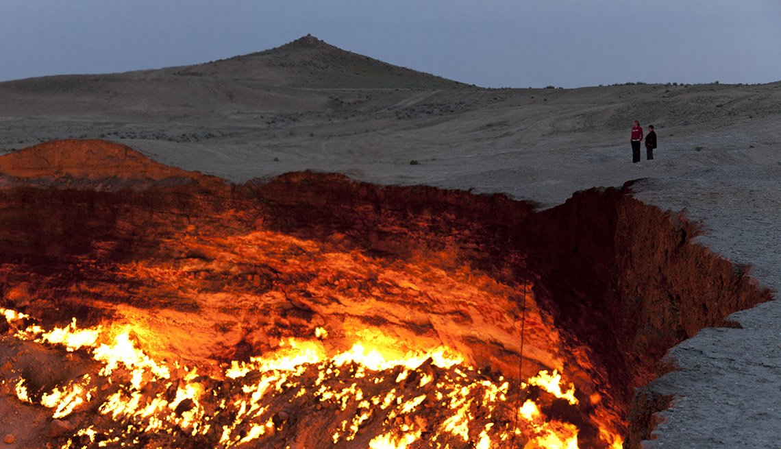 Tourists Stand And Watch The Burning Fires Of The Crater Known As The Door To Hell At Derweze In Turkmenistan, Unique World Travel