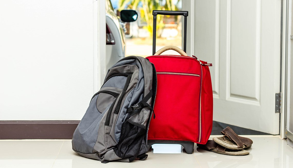 Red Roller Luggage Next To BackPack, Emergency Travel Tips