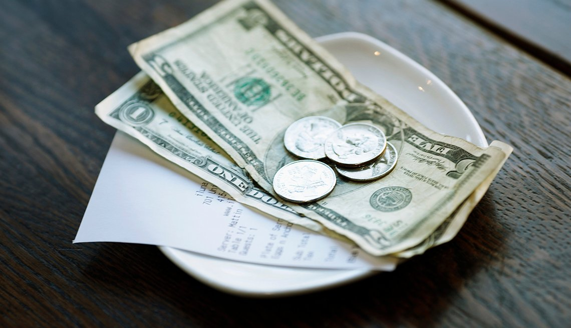 Dollars and Coins Change, Receipt in Change Dish, How to Tip When You're Traveling in the U.S.
