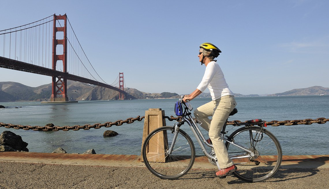 Caucasian Middle-Aged Woman Bikes By The Golden Gate Bridge In San Francisco California, Vacationing Solo