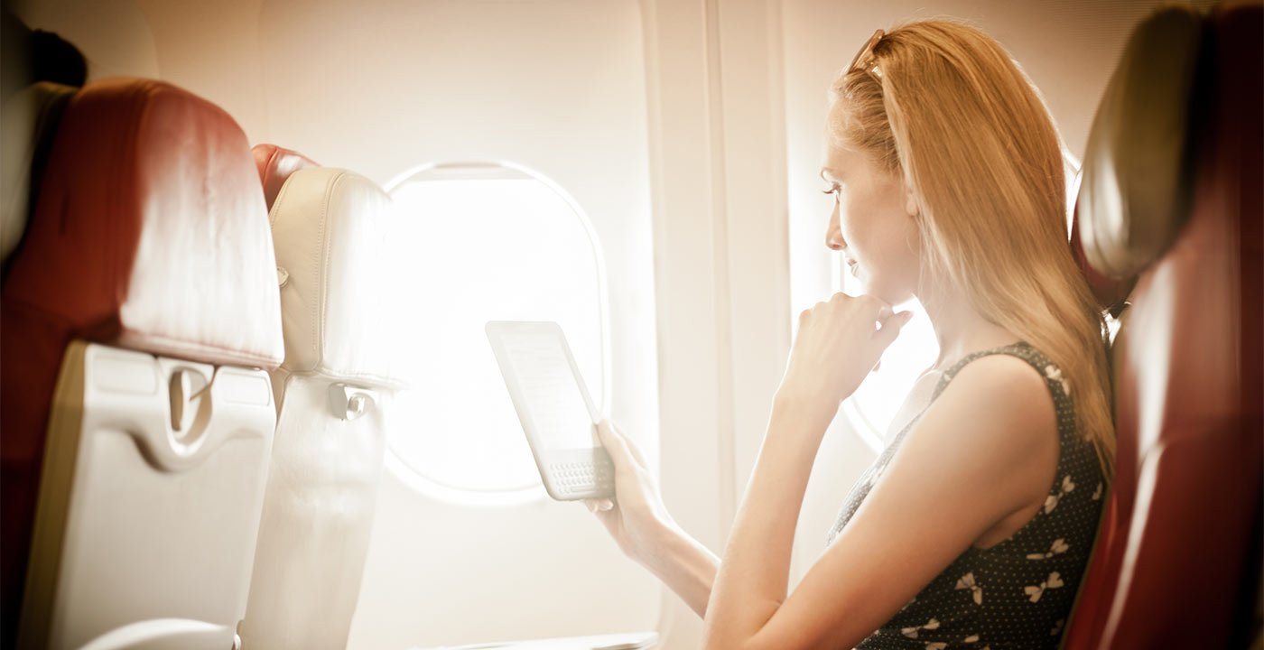 Woman Reads a Tablet on Flight, Bright Window Light, Ridiculous Flying Fees and How to Avoid Them