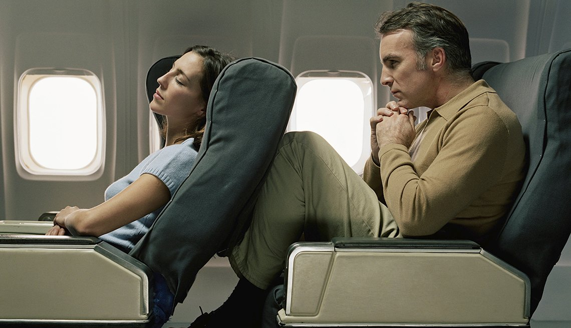 Man with Legs Raised, Woman Sleeps in Airplane Seat, Coach Passengers Get the Squeeze