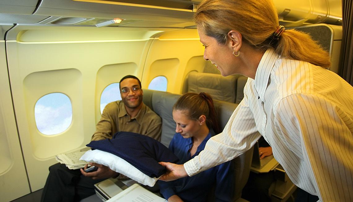 Una azafata entrega una almohada y mantas a un pasajero en un avión.