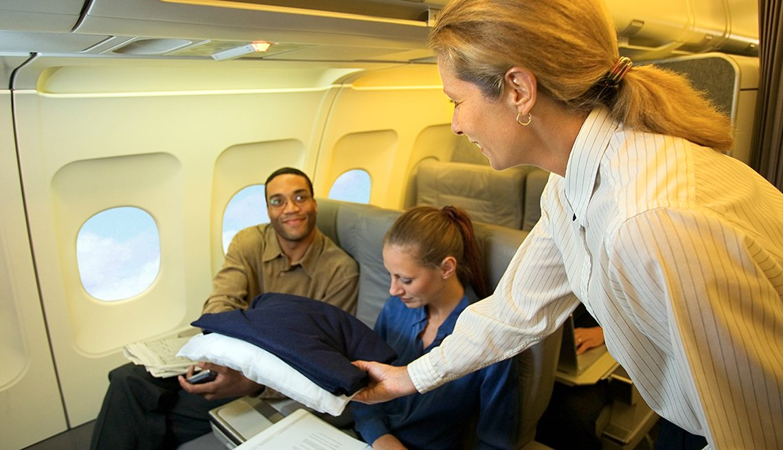 Flight Attendant Hands Blankets Passenger, Airplane Cabin, The Skies Are Friendly After All