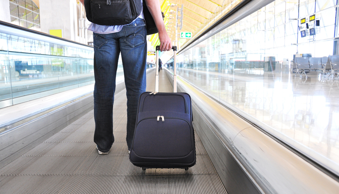 Man with Rolling Suitcase on Moving Airport Walkway, Samantha Brown's Tips for Choosing Luggage