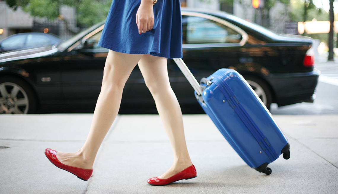 Woman in Blue Skirt Walking on Sidewalk, Blue Carry-on Wheeled Suitcase, Samantha Brown's Tips for Choosing Luggage