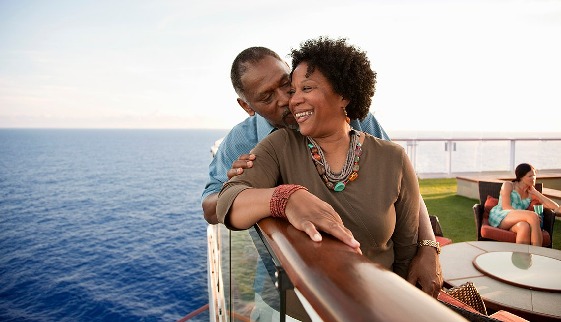 African American Couple Snuggle, Railing of Cruise Ship, Strategies for Scoring Last-Minute Travel Deals