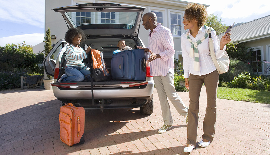 African-American Family Loading Car Road Trip, Tips to Keep Your Home Safe While You're Away