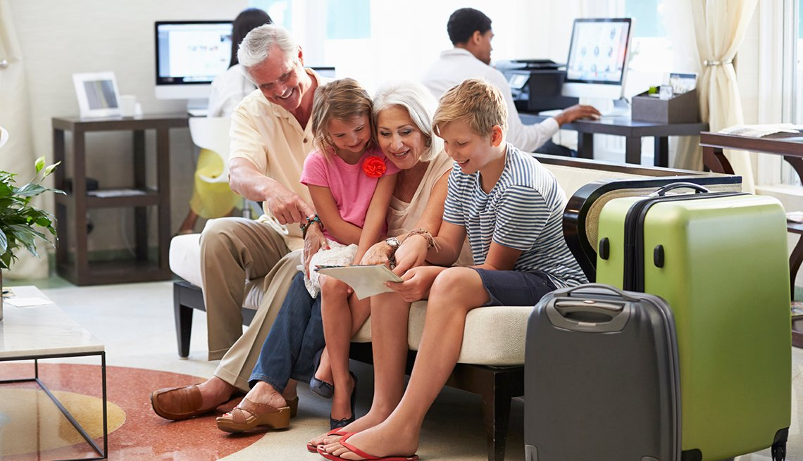 Grandparents With Grandchildren Arriving In Hotel Lobby, How to Plan a Stress-Free Multigenerational Vacation