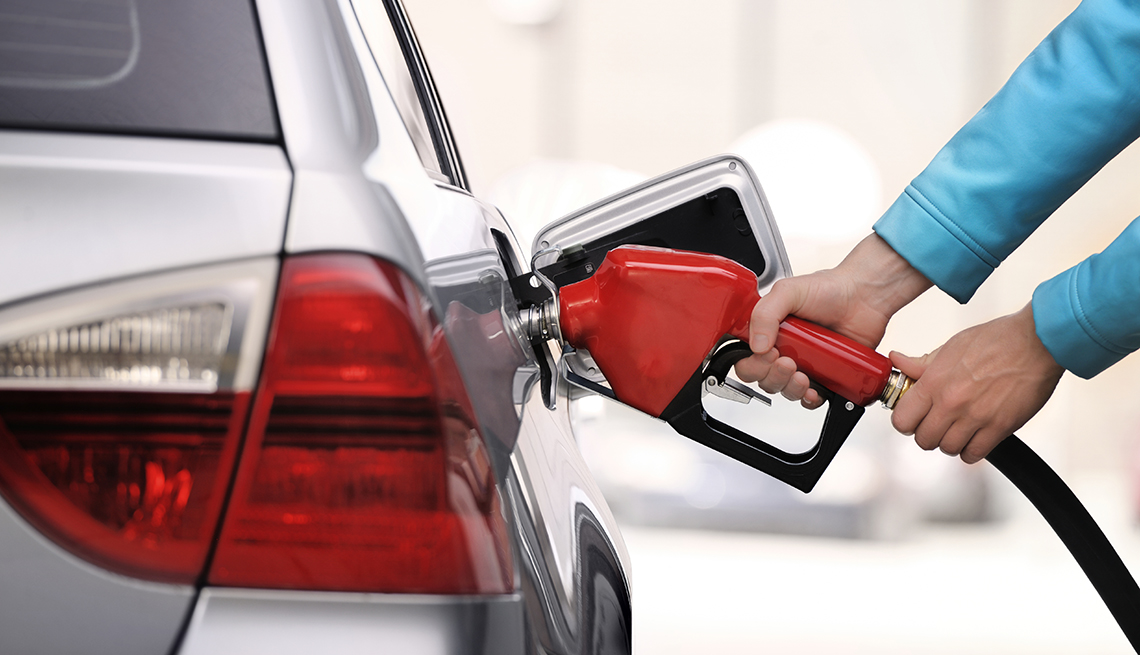 Hands Red Fuel Nozzle, White Car, Tips for Stretching Your Car Rental Dollars