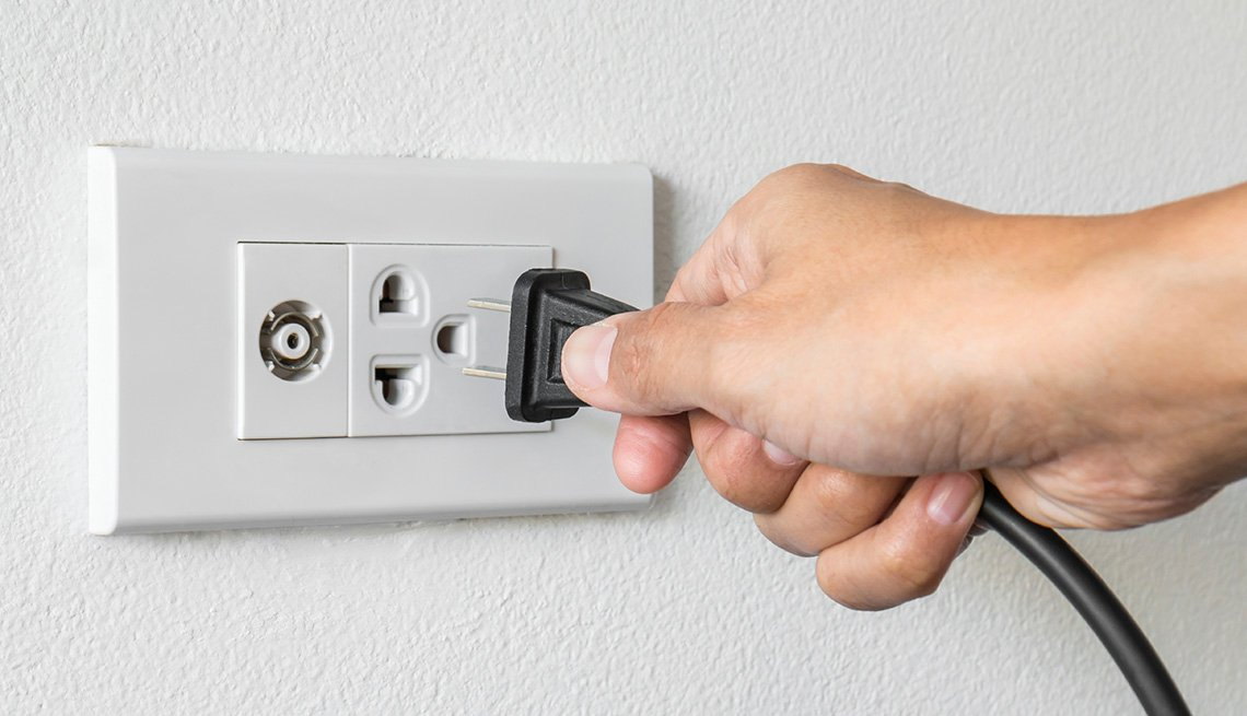 Female Hand, Appliance Plug Electrical Outlet, Tips to Keep Your Home Safe While You're Away