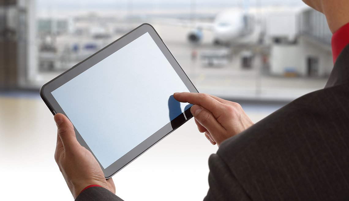 Close Up Of Business Person In Airport Using An Ipad, How To Avoid Getting Hacked While Traveling