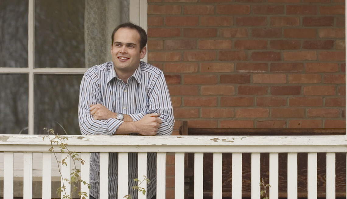 Man on a Porch, Brick House White Railing, Tips to Keep Your Home Safe While You're Away