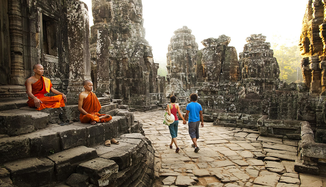 Couple Of Tourists Walk Through Temple Ruins With Monks Praying, Empty Nest To No Nest