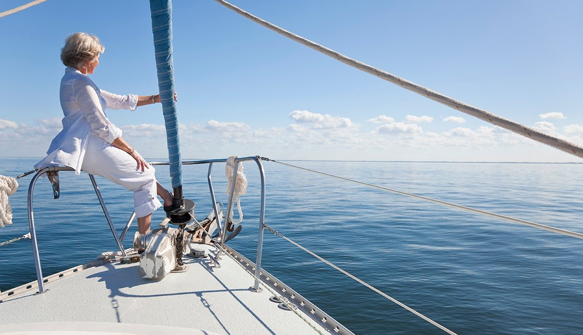 Senior Caucasian Woman Dressed White, Bow of Sailboat, Great All-Inclusive Vacations