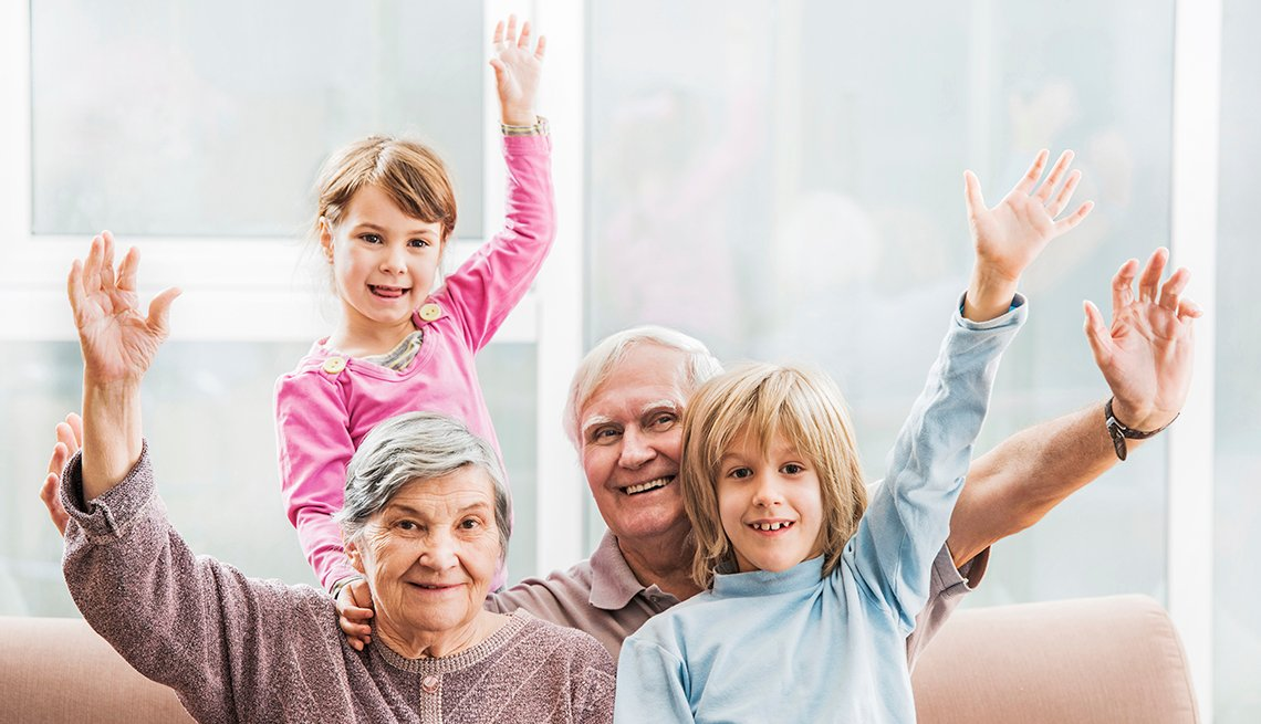 Caucasian Children Grandparents on Couch, Hands Raised, How to Plan a Stress-Free Multigenerational Vacation