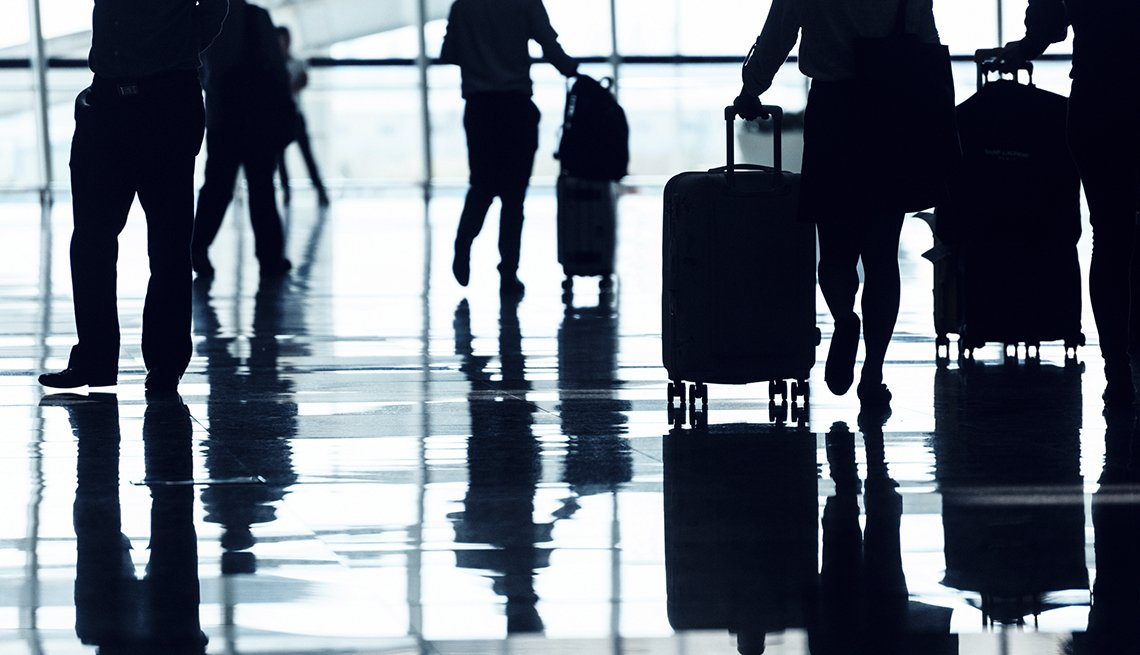 Passengers Navigate Through Busy Airport Terminal With Luggage Reflected In Floor Surface, Navigate Airports