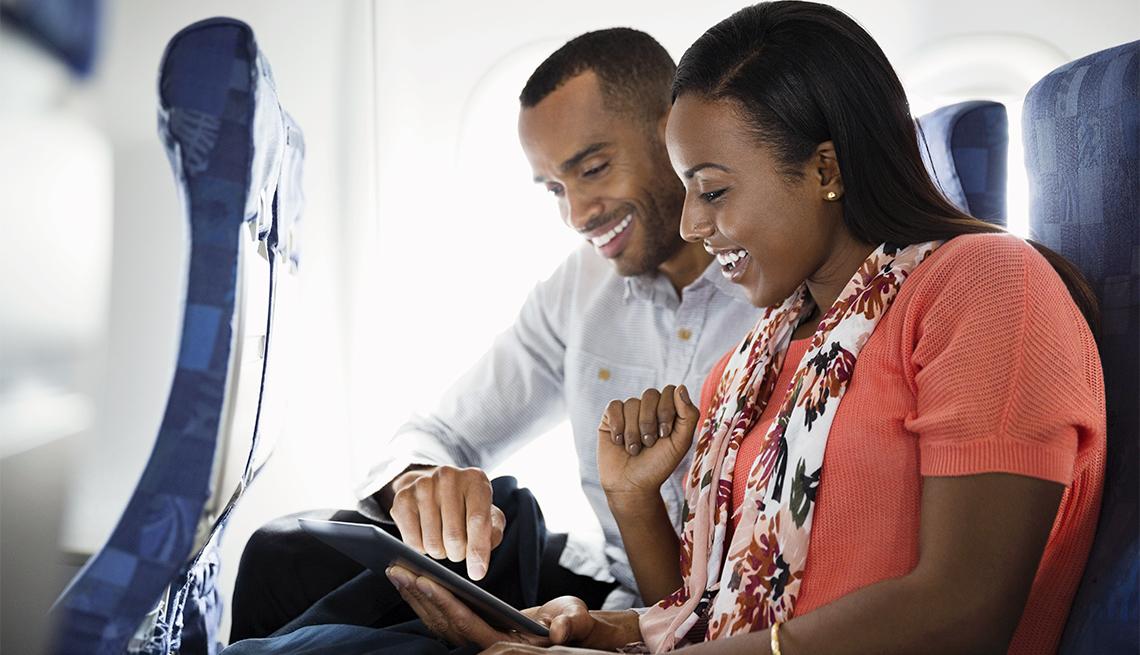Artefactos de tecnología para llevar en tu próximo viaje - Pareja usando una tableta electrónica