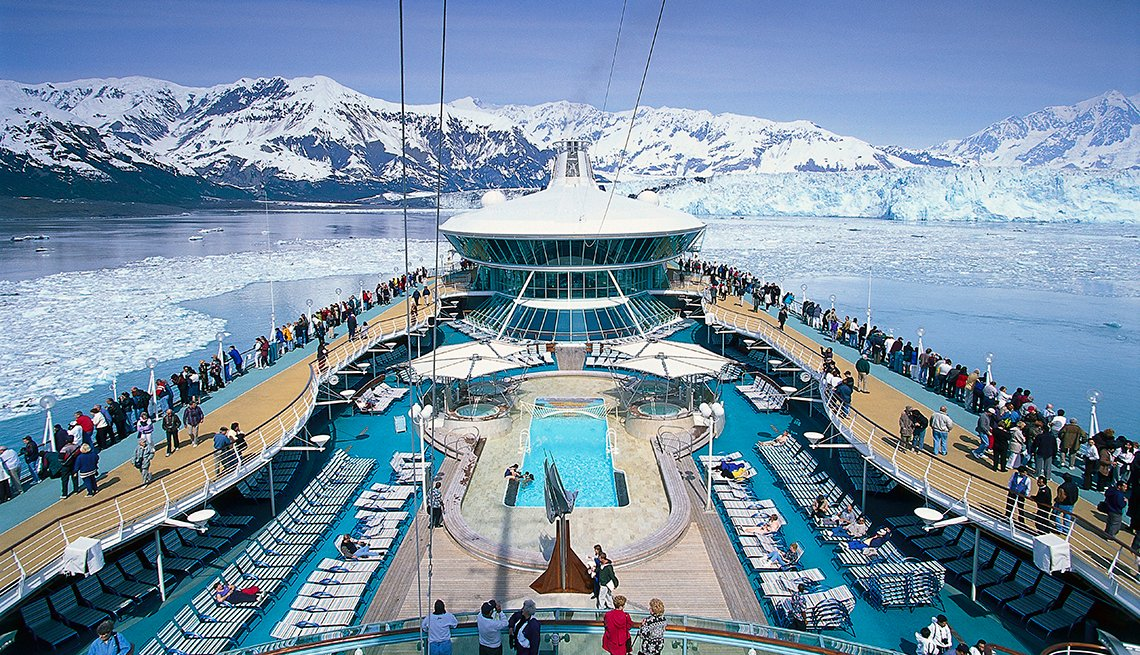 View of deck of cruise ship with snowy mountains in the distance