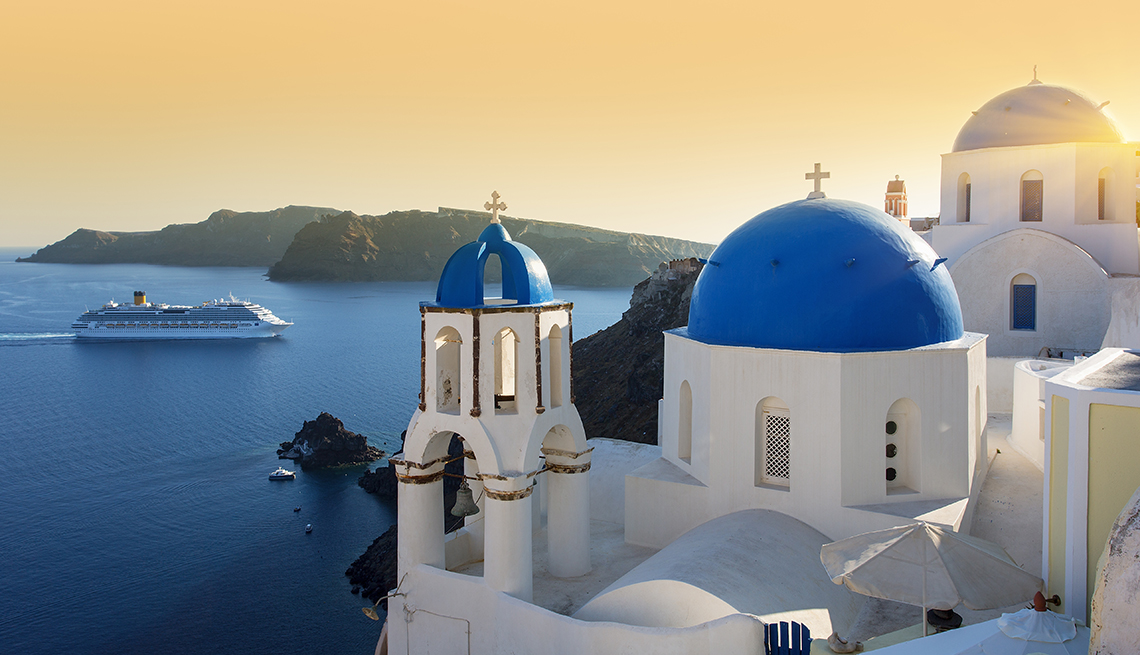 A cruise ship in the distance with a blue-domed church in the foreground