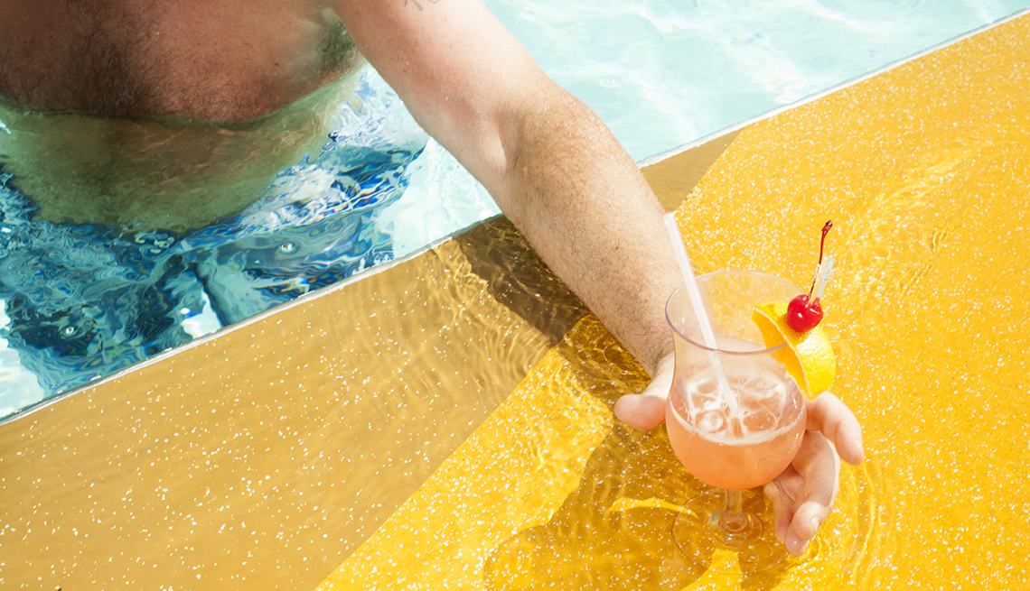 Man reaching for a tropical drink from a pool