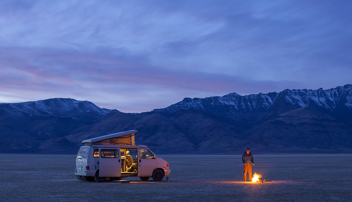 A man standing by a campfire near a camper van on a wide expanse of a valley at dusk