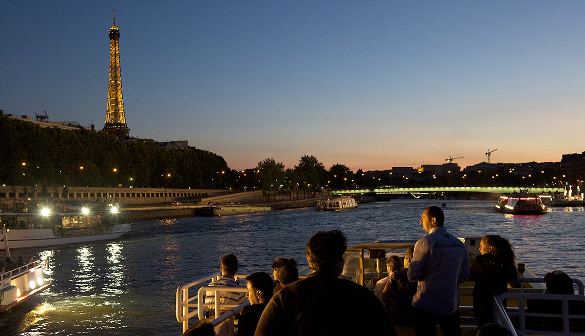 Travelers cruising the Seine River at dusk in summer, view of Eiffel Tower in distance