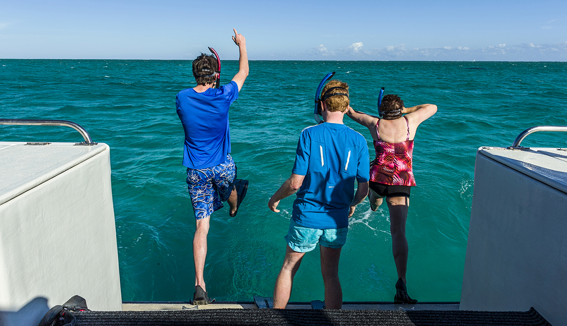 Tourists leap of the rear of a boat with snorkels on