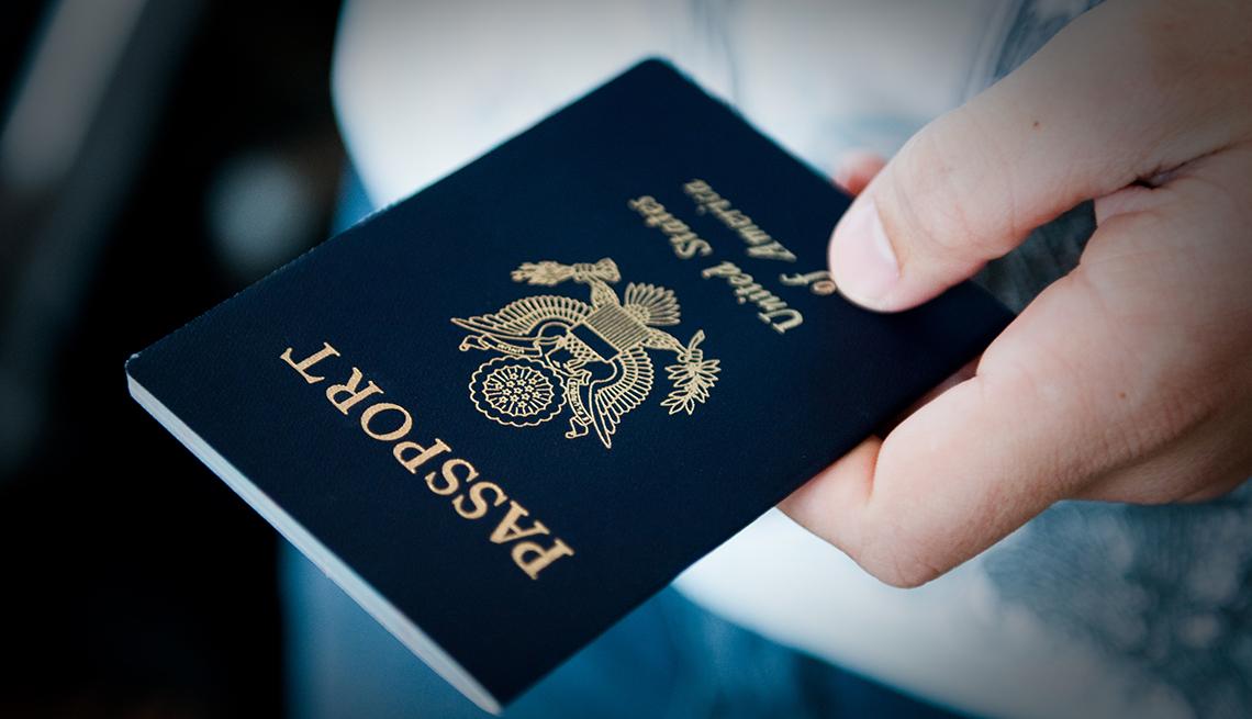 Persona sostiene un pasaporte en la mano.