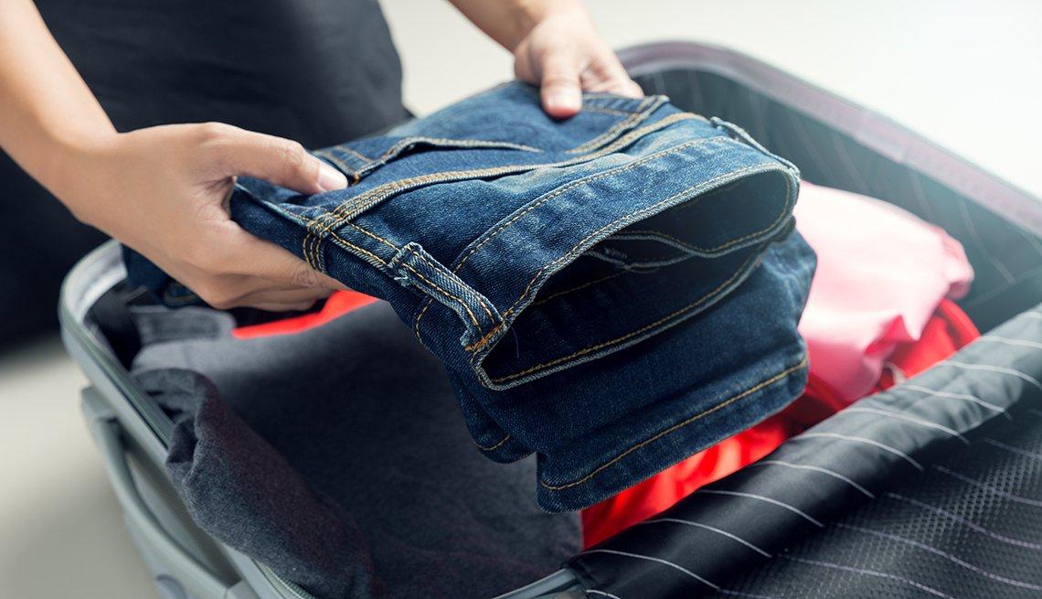 Mujer empaca ropa en una maleta de viaje.