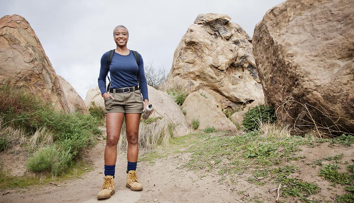 Mature woman standing between mountain rocks