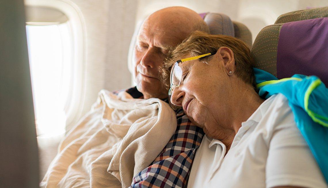 Pareja mayor de turistas durmiendo en el asiento de un avión.