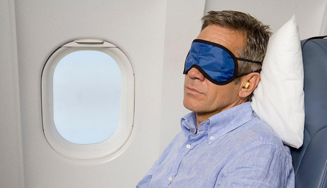 Un hombre duerme en un avión.