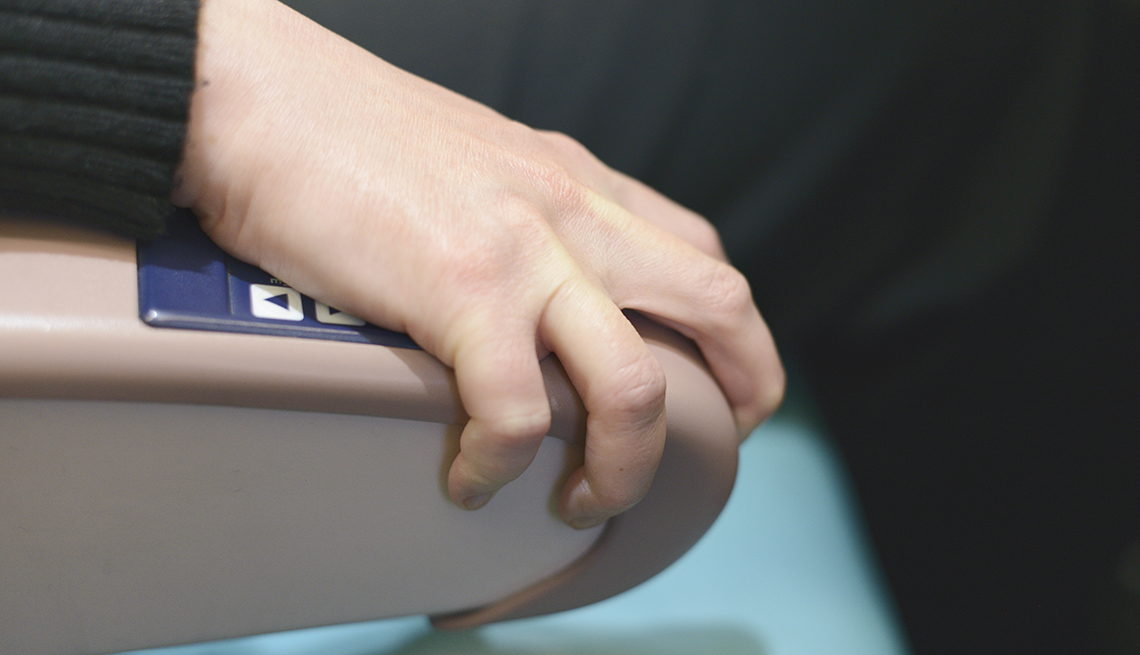 A female passenger on a plane grips the seat armrest from fear of flying